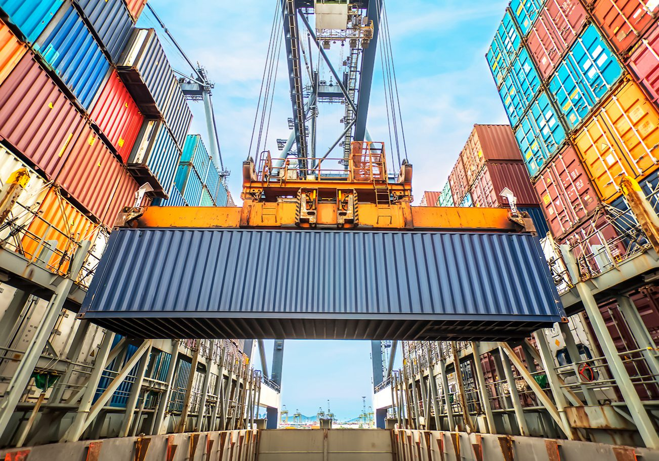 Industrial crane loading Containers in a Cargo freight ship; Shutterstock ID 214476049
